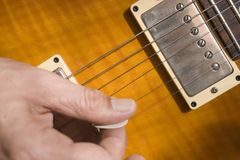 Playing guitar. Closeup of a hand holding pick, playing a guitar Royalty Free Stock Photo