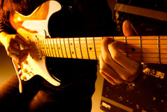 Playing guitar. Musician playing guitar at studio with shallow depth of field and orange lighting stock photography