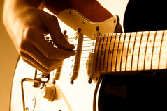 Playing guitar. Hand picking guitar strings with shallow depth of field and orange lighting Stock Image