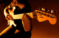 Playing guitar. Musician playing guitar at studio with shallow depth of field and orange lighting Royalty Free Stock Photos