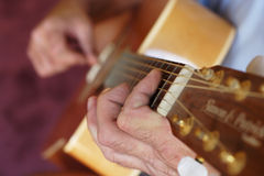 Playing the guitar. Man playing a guitar, focus on the hand holding the fretboard stock photography