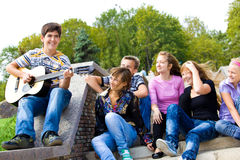 Playing guitar. Cute teenage guy playing guitar for his friends Stock Photos