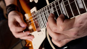 Playing guitar. Close-up view of hands playing electric guitar Royalty Free Stock Image