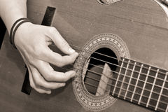 Playing guitar. Sepia image of a lady playing guitar Stock Photos