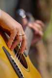 Playing the guitar. Guitar, strings, arms, fingers of a guitar player, with blurry background Stock Image