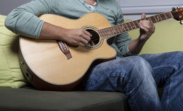 Playing guitar. A guy is playing acoustic guitar on the couch Royalty Free Stock Images