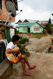 Playing guitar. A lepcha teenager boy is playing Hawaiian guitar in front of his house at Rishap Village near Darjeeling, India. Rishap small village on the hill Royalty Free Stock Images