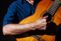 Playing the guitar. A human hand foreground playing the classical guitar Royalty Free Stock Image
