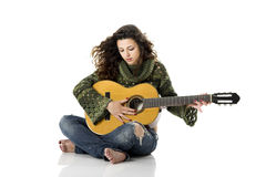 Playing guitar. Beautiful woman isolated on white playing music with a guitar Royalty Free Stock Image