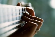 Playing the guitar. Close-up of a girl playing the guitar Stock Photography