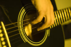 Playing guitar. Shot of hands playing an acoustic guitar stock photography