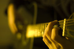 Playing guitar. Shot of hands playing an acoustic guitar royalty free stock photo