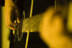 Playing guitar. Shot of hands playing an acoustic guitar stock image