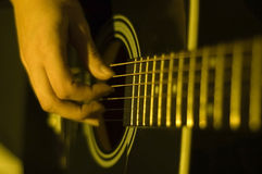Playing guitar. Shot of hands playing an acoustic guitar royalty free stock images