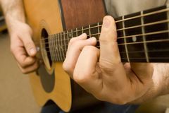 Playing Guitar. Close up on the chord while a musician plays guitar Royalty Free Stock Images