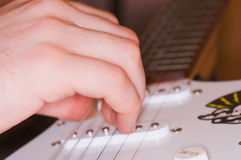 Playing guitar. Close up of a hand playing a guitar Stock Image