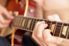 Playing guitar. Man's hands holding and plaing the guitar Royalty Free Stock Images
