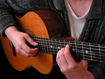 Playing guitar. Playing acoustic guitar, closeup Royalty Free Stock Images