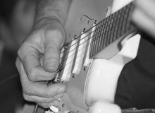 Playing guitar. Closeup of a mans weathered hand playing Fender Stratocaster Guitar royalty free stock photos