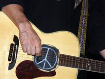 Playing guitar. A hand strumming acoustic guitar with peace sign Royalty Free Stock Photo