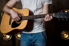 Playing guitar. Acoustic guitar in the hands of the guitarist. Horizontal frame Royalty Free Stock Image