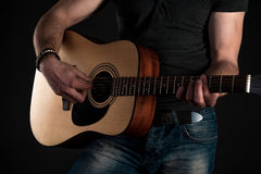 Playing guitar. Acoustic guitar in the hands of the guitarist. Horizontal frame Royalty Free Stock Photography