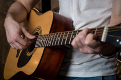 Playing guitar. Acoustic guitar in the hands of the guitarist. Horizontal frame Stock Photography