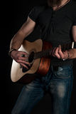 Playing guitar. Acoustic guitar in the hands of the guitarist. Vertical frame Stock Image