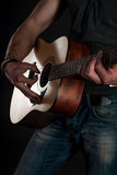 Playing guitar. Acoustic guitar in the hands of the guitarist. Vertical frame Royalty Free Stock Images