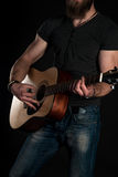 Playing guitar. Acoustic guitar in the hands of the guitarist. Vertical frame Royalty Free Stock Photos