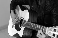 Playing guitar in black and white. Picture of a musician playing guitar in black and white stock photography