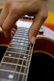 Playing guitar close-up. Playing bright colourful guitar close-up Royalty Free Stock Photo