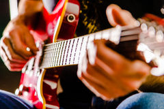 Playing guitar. Close up of hands strumming red guitar Royalty Free Stock Photos