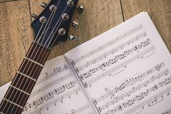 Playing guitar... Close-up photo of guitar neck and music notes against of wooden background. Musical instruments. Music equipment royalty free stock photo