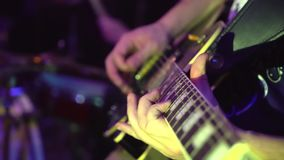 Close up of a mans hand strumming the strings of a guitar. slow-motion. Playing guitar close-up slow motion macro. Guitarist hands pressing chords with fingers stock footage