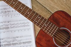 Playing Guitar. Close up view of brown acoustic guitar with music notes against wooden floor stock image