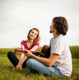 Playing guitar - dating couple. Young men playing to his girlfriend on guitar in nature - dating couple outdoor lifestyle Stock Image