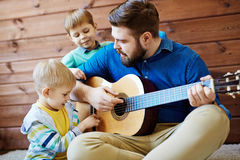 Playing guitar with father Stock Photography