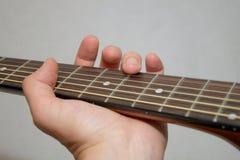 Playing guitar: flageolet finger touch on string. Educational or tutorial illustration: left hand playing acoustic guitar by finger touching a string - flageolet Stock Images