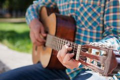 Playing guitar. Handsome guy teenager playing guitar on the street Royalty Free Stock Images