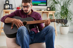 Playing guitar. Handsome young man in glasses playing guitar Royalty Free Stock Image