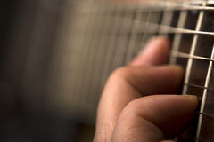 Playing the guitar. Horizontal close up of a hand playing the guitar with shallow depth of field Stock Image