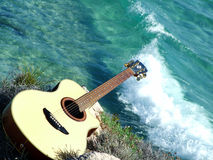 Playing guitar looking the sea stock image