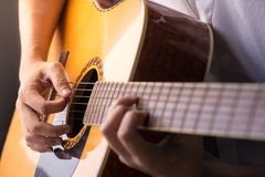 Playing guitar. A man sitting and playing classic wooden guitar close up to chord tab fretboard Stock Images