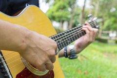Playing guitar in the park Stock Images