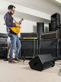 Playing guitar in the recording studio. Photo of a man playing his electric guitar in a recording studio in front of amplifiers Royalty Free Stock Photography
