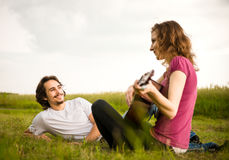 Playing guitar - romantic couple Stock Photos
