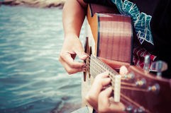 Playing guitar on seaside Royalty Free Stock Image
