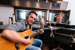 Playing guitar and singing. Hispanic man playing guitar and singing in the recording studio Stock Image