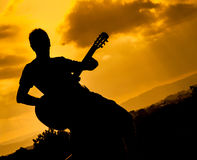 Playing guitar at sunset Royalty Free Stock Images